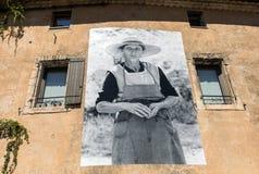 有描述古板的生活的场面广告牌的一个典型的老石房子在戈尔代村庄,横谷,普罗旺斯, 库存图片