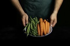 有提出菜和庭院菜的绿色围裙的人 库存图片