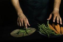有提出菜和庭院菜的绿色围裙的人 免版税库存照片