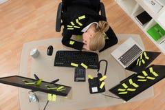 有提示笔记的女实业家睡觉在办公室的 免版税库存照片