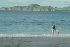 有握他的儿子的手的背包的父亲由海 他们进入水反对美丽的海岛背景  库存照片