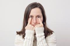 有握她的在眼睛前面的长的头发的女孩手指 免版税库存图片
