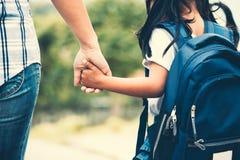 有握她的母亲手的背包的亚裔女孩 图库摄影
