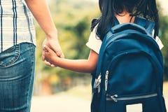 有握她的母亲手的背包的亚裔女孩 免版税图库摄影