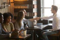 有握手的微笑的男性经纪问候顾客在咖啡馆我 免版税库存照片