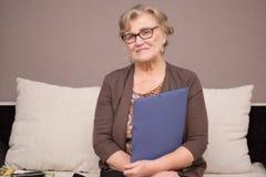 有握手的文件夹的老妇人 免版税库存图片