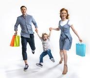 有握手的购物袋的父母与在白色隔绝的激动的儿子一起 免版税库存图片