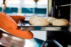 有握持热锅的布垫子的贝克手在金属甜酥饼干旁边 免版税库存图片