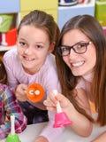有握音乐手铃的逗人喜爱的孩子的微笑的老师 免版税库存照片