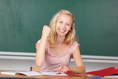有握紧拳头的女老师在书桌 免版税库存照片