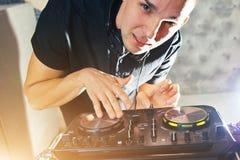 有搅拌器的年轻人DJ工作 图库摄影