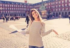有搜寻新的地方的地图的愉快的年轻旅游妇女在西班牙 在欧洲概念附近的旅游业方面 免版税库存照片