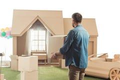 有搬入新的纸板房子的箱子的人 免版税库存照片