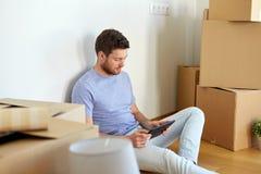 有搬到新的家的片剂个人计算机和箱子的人 免版税图库摄影