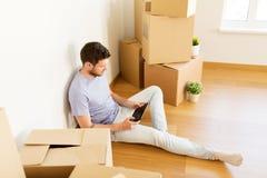 有搬到新的家的片剂个人计算机和箱子的人 免版税库存图片