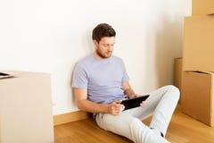 有搬到新的家的片剂个人计算机和箱子的人 免版税库存照片