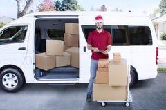 有搬运车和包裹的送货人 免版税图库摄影