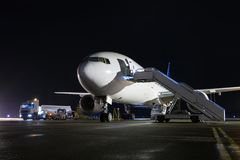 有搭乘台阶的大型乘客飞机在晚上a 免版税库存照片