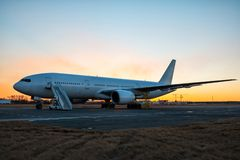 有搭乘步的白色宽身体乘客飞机在平衡微明的机场围裙 库存图片