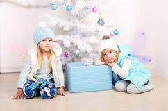 有摆在一棵装饰的圣诞树旁边的金发的逗人喜爱的小女孩 免版税库存照片