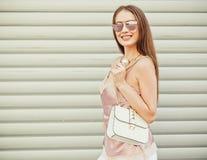 有摆在与一个相当一点袋子的太阳镜的美丽的时兴地加工好的深色头发的女孩在白色墙壁附近 免版税库存图片