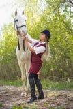 有摆在与一匹红色马的长的头发的美丽的深色的女孩在森林里 免版税库存图片