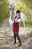 有摆在与一匹红色马的长的头发的美丽的深色的女孩在森林里 库存照片