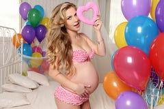有摆在与五颜六色的空气轻快优雅的金发的孕妇和装饰心脏 库存图片