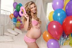 有摆在与五颜六色的空气轻快优雅的金发的孕妇和装饰心脏 库存照片