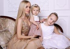 有摆在与可爱的逗人喜爱的d的长的金发的华美的母亲 库存照片