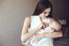 有摆在与她的小可爱的婴孩的长的黑发的美丽的年轻母亲 库存照片