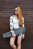 有摆在与longboard的美好的图的偶然穿戴的女性行家在夏天 库存图片