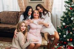 有摆在为照相机的三个美丽的女儿的妈妈 库存照片