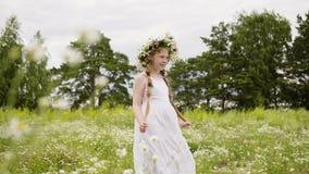 有摆在为照相机的雏菊花圈和白色礼服的青少年的女孩在花草甸 影视素材