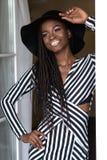 有摆在为照相机的黑暗的发光的皮肤的可爱的性感的女孩支持接触她的帽子的窗口 免版税库存照片