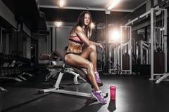 有摆在健身房的长凳的振动器的健身女孩 图库摄影