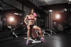 有摆在健身房的长凳的振动器的健身女孩 免版税库存图片