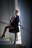 有摆在台阶的萨克斯管和长的腿的性感的可爱的妇女 年轻有吸引力的白肤金发的使用的萨克斯管 hornsection仪器音乐零件萨克斯管 爵士乐 免版税库存照片