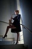 有摆在台阶的萨克斯管和长的腿的性感的可爱的妇女 年轻有吸引力的白肤金发的使用的萨克斯管 hornsection仪器音乐零件萨克斯管 爵士乐 库存图片