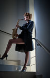 有摆在台阶的萨克斯管和长的腿的性感的可爱的妇女 年轻有吸引力的白肤金发的使用的萨克斯管 hornsection仪器音乐零件萨克斯管 爵士乐 库存照片