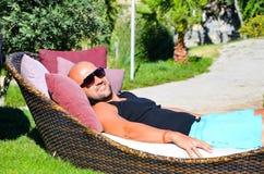 有摆在和放松在一个热带庭院里的太阳镜的美丽的肌肉被晒黑的微笑的人 库存图片