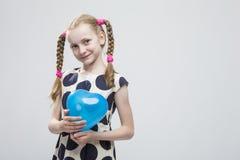 有摆在圆点礼服的猪尾的白肤金发的女孩反对白色 拿着蓝天气球 图库摄影