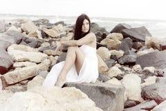 有摆在坐岩石的白色礼服的微笑华美的夫人看海洋愉快的减速火箭的样式 库存照片