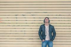 有摆在城市街道的耳机的年轻英俊的人 图库摄影