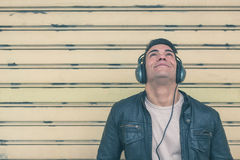 有摆在城市街道的耳机的年轻英俊的人 库存照片