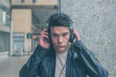 有摆在城市街道的耳机的年轻英俊的人 库存图片