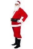 有摆在大的腹部的确信的圣诞老人斜向一边 免版税库存照片