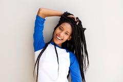 有摆在对墙壁的结辨的头发的可爱的年轻黑人妇女 免版税库存照片