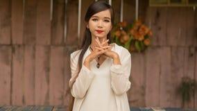 有摆在对有人为玫瑰的墙壁的长的头发的越南年轻深色的女孩 河内 免版税图库摄影