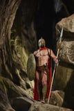 有摆在岩石的武器的强有力的战士 图库摄影